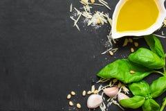 Green basil pesto - italian recipe ingredients on black chalkboard background. Parmesan cheese, basil leaves, pine nuts, olive oil, garlic, salt. top view stock image