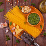 Green basil pesto - italian recipe ingredients on wooden table. Stock Image