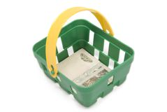 Green basket with a banknote inside. A small green basket with a yellow handle and a 10 rouble banknote inside against white background royalty free stock image