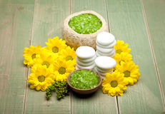 Green bath salt and yellow flowers Royalty Free Stock Images