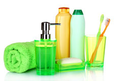Green bathroom accessories, shampoo and towel. Over the white Stock Photos