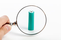 Green battery and magnifying glass Stock Photos