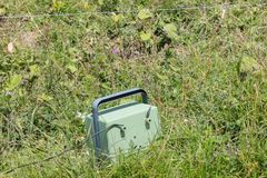Green battery powering an electric fence Stock Photos