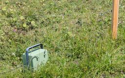 Green battery powering an electric fence Stock Photo
