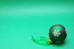 Green bauble. Green Christmas bauble lying on green background Stock Photography