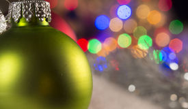 Green bauble. Close up of a green bauble lights blurred in background royalty free stock photo