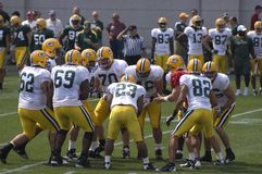 Green Bay Packers NFL Football Training Camp Scene. Players from the Green Bay Packers huddling up on the practice field. NFL football stock photo