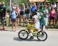Green Bay Packer Player Riding Bike with Young Fan stock image