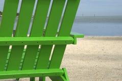 Green Beach Chair. A bright green beach chair sits on a warm, tropical beach Stock Photos