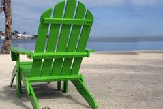 Green Beach Chair. A lone neon green beach chair breaks the monotony of a natural toned beach Stock Photo