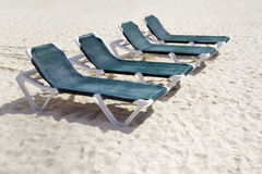 Green Beach Chairs. Rows of several green lounge chairs on the beach Stock Image