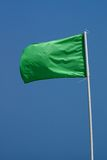 Green Beach Flag. Against Blue Sky Stock Photo