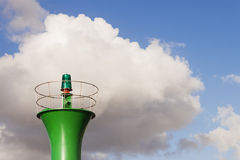 Green beacon light. Green beacon top light against a blue sky with white clouds Stock Photo