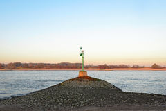 Green beacon in the river Waal Stock Photo