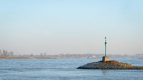 Green beacon in the river Waal. In the evening sun Royalty Free Stock Photography