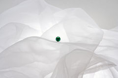 Green bead. The green bead on a white fabric Stock Photography