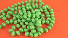 Green beads necklaces on orange isolated. Green beads necklaces on orange background for female person stock footage