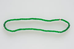 Green beads with one another. String/ chaplet of green glass beads with one silver pearl, on white background Royalty Free Stock Photos