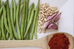 Green beans. With some garlics, paprika powder in wooden spoon and pine nuts on white plate Stock Photography