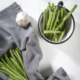 The Green beans in an aluminum cup, napkin and garlic on a white wooden table. Autumn recipes. Copy space. Green beans in an aluminum cup, napkin and garlic on a Stock Photography