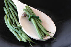 Green Beans Bundled. French green beans bundled with chives resting on wooden spoon Royalty Free Stock Photos