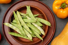 Green beans in clay plate with vegetables