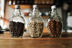 Green beans and Coffee beans inside the clear bottle , Focus onl Stock Photos