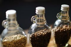 Green beans and Coffee beans inside the clear bottle , Focus onl Royalty Free Stock Photo