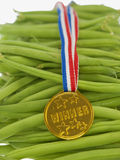 Green beans with a gold medal Stock Images