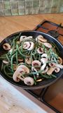 Green beans and mushrooms. French green beans and chopped mushrooms in frying pan on gas stove in family kitchen Royalty Free Stock Images