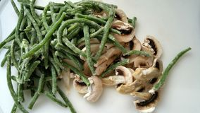 Green beans and mushrooms waiting to be cooked. Frozen French green beans and chopped fresh mushrooms on chopping board in preparation for cooking Royalty Free Stock Image
