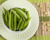 Green Beans Pods on Bamboo Placemat. With individual peas. Pods are placed in a white ramekin on a green plate Royalty Free Stock Photos