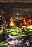 Green beans pods cooking ingredients in bows on rustic kitchen table Royalty Free Stock Photos