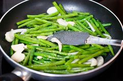 Green beans with onion and garlic ready for cooking in frying pan. Close up view of green beans on a frying pan royalty free stock photography