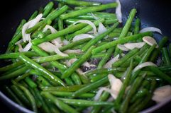 Green beans with onion and garlic ready for cooking in frying pan. Close up view of green beans on a frying pan stock photos