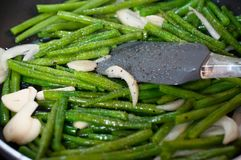 Green beans with onion and garlic ready for cooking in frying pan. Close up view of green beans on a frying pan royalty free stock image