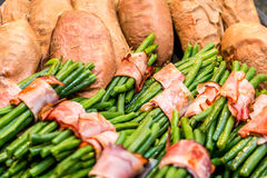 Green beans rolled in bacon and baked sweet potatoes Stock Photo