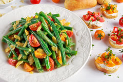 Green beans salad with Red, Yellow Tomatoes, bruschettas and flaked almond on white plate Royalty Free Stock Photography