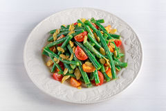 Green beans salad with Red, Yellow Tomatoes, bruschettas and flaked almond on white plate Royalty Free Stock Image