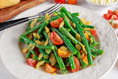 Green beans salad with Red, Yellow Tomatoes, bruschettas and flaked almond on white plate Royalty Free Stock Images