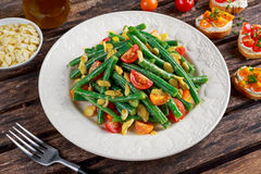 Green beans salad with Red, Yellow Tomatoes, bruschettas and flaked almond on white plate Stock Photo