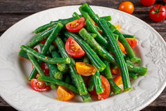 Green beans salad with Red, Yellow Tomatoes on white plate Stock Images
