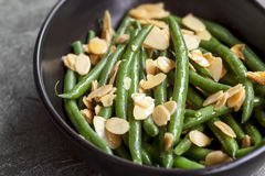 Green Beans with Toasted Almonds in Black Bowl. Green beans with toasted almonds, in black bowl over dark slate Royalty Free Stock Photography