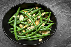 Green Beans with Toasted Almonds in Black Bowl. Green beans with toasted almonds, in black bowl over dark slate.  Overhead view Stock Photo