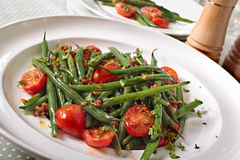 Green beans and tomato salad on white plate Stock Photos