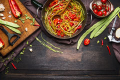 Green beans with tomatoes sauce in cooking pot with ingredients on cutting board for vegetarian dish on dark rustic wooden backgro Stock Photos