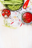 Green beans with tomatoes sauce, cooking  preparation on light wooden background with traditionally embroidered cloth and ingredie Stock Photo