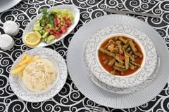 Green beans. White bowl with cooked green beans in a tomato sauce stock images
