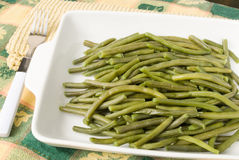 Green beans in a white casserole dish with Thanksgiving tableclo. Homemade cooked string green beans served in a white casserole dish. There is a fork lying to Stock Photo