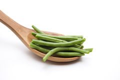 Green beans on wooden spoon. And on white background stock image